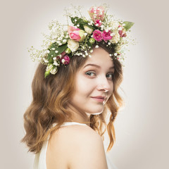 Beautiful young woman in a floral wreath of roses