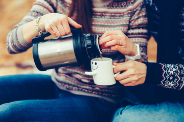 A man and a woman, covered with a blanket, sitting outdoors, holding a thermos and mugs with tea. A guy and a girl in jeans and sweater, sitting on a blanket, enjoying nature. Vintage tonted photo.