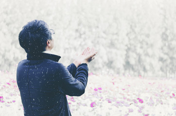 Back view of a young man while standing in the snowy field