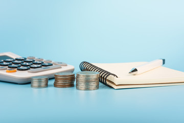 stack of coin notebook pen and calculator on light blue background with copy space. planning save for concept.