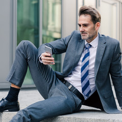 businessman sitting on stairs in an office park