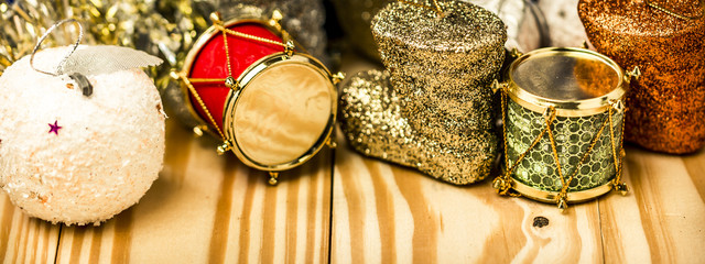 Merry Christmas and New year Decoration with red, green, gold drum, winter boots and white apple. Copyspace above real textured pine wood plank with beautiful natural pattern. Selective focused.