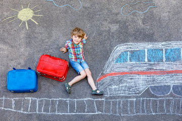 Little kid boy having fun with fast train picture drawing with colorful chalks on asphalt