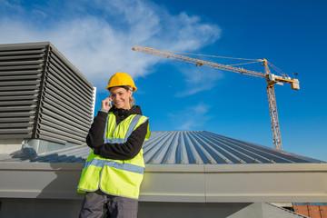 female ingineer with hardhat using electronics on construction roof