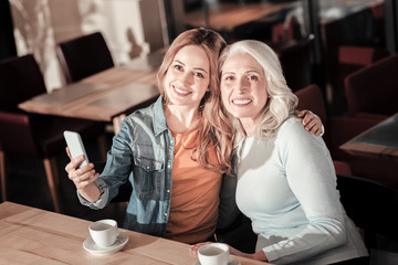 Happy together. Kind pleasant cheerful woman looking glad while sitting in a cafe and hugging her beautiful elderly granny