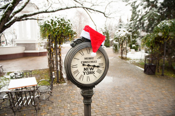 vintage street clock with text Merry Christmas New York and Santa Claus hat on them outdoor in new york central park