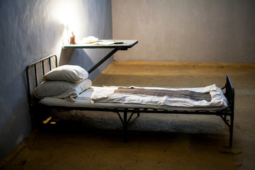 Dark prison cell with bed at night