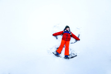 Cute little kid boy in colorful winter clothes making snow angel, laying down on snow