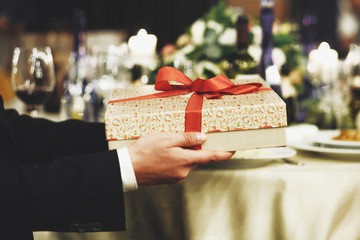 Man holds present box with red ribbon in his arms sitting at the dinner table