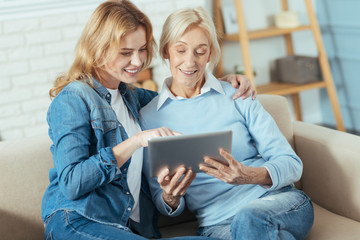 Look here. Positive cheerful young woman sitting with her attentive senior grandmother and showing her photos on the screen of a modern convenient tablet