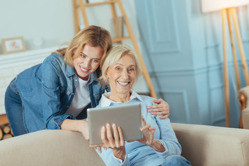 Very funny. Happy senior woman holding a convenient modern tablet and laughing while her granddaughter standing behind her and gently touching her shoulder