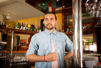 Handsome young bartender holds cocktail glass posing for camera.