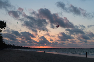 Drachenfliegen am Strand beim Sonnenuntergang