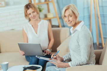 Cheerful client. Smart responsible attentive aged woman smiling while checking all the documents with her experienced professional financial advisor sitting with a laptop and looking at her