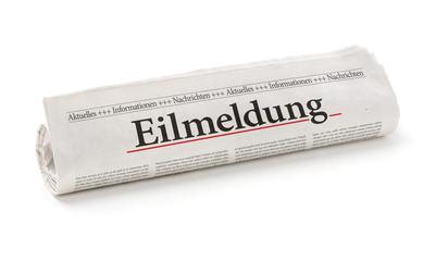 Zeitungsrolle mit der Überschrift Eilmeldung
