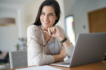 Cheerful woman working on laptop at home-office