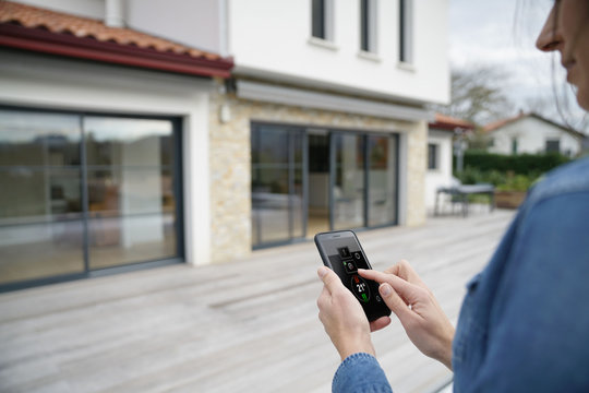 Woman using remote home control system on smartphone