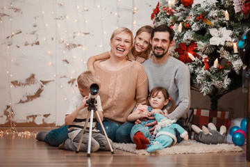 New Year's picture of family sitting at decorated Christmas tree