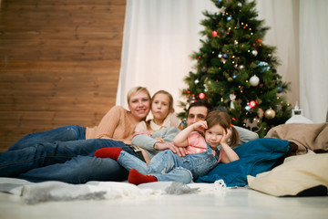 Photo of happy family with two daughters lying on floor against backdrop of New Year's decorations