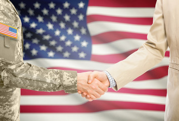 USA military man in uniform and civil man in suit shaking hands with adequate national flag on background - United States of America
