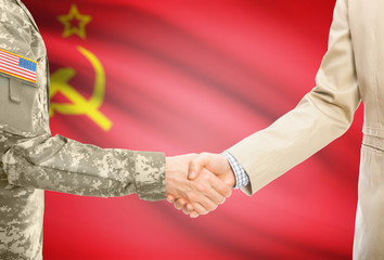 USA military man in uniform and civil man in suit shaking hands with adequate national flag on background - Soviet Union - USSR