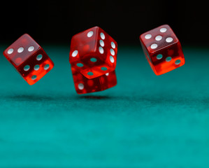 Photo of several red dice falling on green table on black background