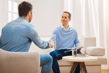Welcome to me. Pleasant merry gay psychologist  welcoming new patient while shaking hands and looking at him
