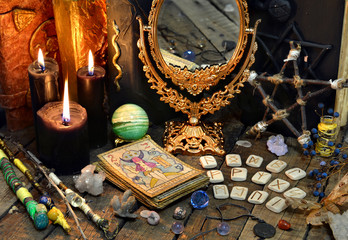 Tarot cards, magic wands, runes, black candles with mirrow and old book. Occult, esoteric, divination and wicca concept. Mystic and vintage background