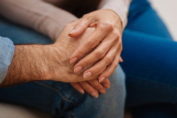 Love everywhere. Close up of  young couples hands caught together  placing them on the knees