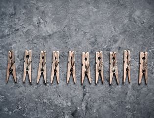 Many clothespins on a concrete surface. Top view.