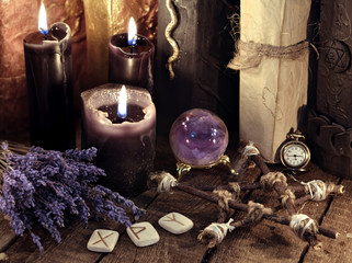 Black candles, pentagram, runes and lavender flowers with crystal ball. Occult, esoteric, divination and wicca concept. Mystic and vintage background