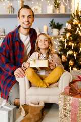 Photo of father and girl with gift background of Christmas decorations in studio