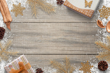 Christmas decorations with snow on wooden board with free space for greeting text. Gifts, fir branches, snowflakes and pinecones.