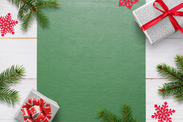 Christmas background with decorations on white wooden table and green tablecloth with free space for greeting text. Gifts, fir branches and snowflake decorations. Top view.