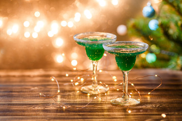 Christmas photo of two wine glasses with green cocktail