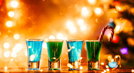 Christmas image of four wine glasses with green cocktail, caramel sticks