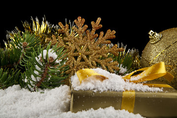 branch of a Christmas tree, gifts and a snowflake in the snow on a black background close-up