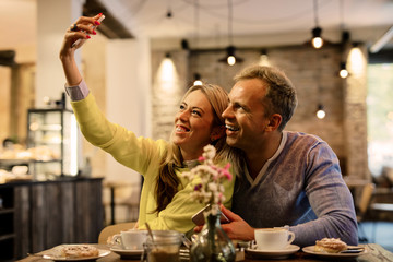 Couple taking selfie in cafe