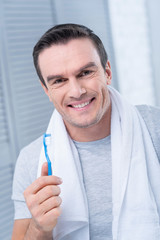 Shiny smile. Prosperous nice young man carrying toothbrush smiling to the camera and preparing for going out