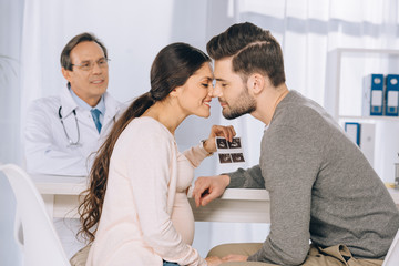 happy couple holding photo of ultrasound diagnostics and kissing