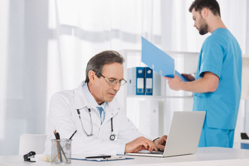 male doctor working at laptop in clinic