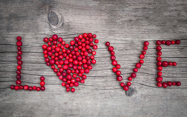 red ripe berries cranberries in the shape of a heart inscription love lie on rustic wooden background closeup. place for text. wooden old background. the concept of love.