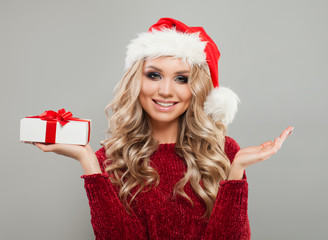 Cheerful New Year Woman with Christmas Gift on Gray Background. Perfect Girl in Santa Hat