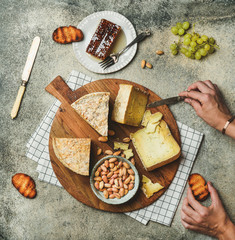 Flat-lay of cheese platter with cheese assortment, green grapes, honey and nuts with female hands reaching to food over grey concrete background, top view. Party or gathering eating concept