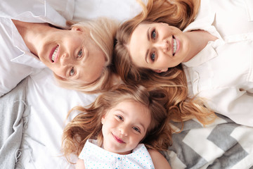 Family unity. Happy delighted positive family looking at you and smiling while lying together