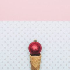 Christmas decoration bauble in ice cream cone. New Year and Christmas minimal concept.