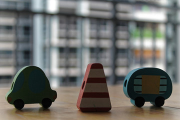 Wooden toy cars with traffic pylon on the table.