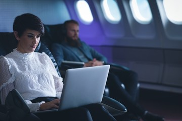 Female executive using laptop in airplane