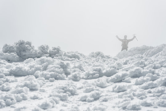 Back view of a man celebrating the summit of a mountain with open arms in the snow on a foggy day