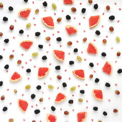Concept of healthy food. Berries and fruit pattern. Slices of grapefruit, blackberries, grains of pomegranate, black and green grapes on a white background.Composition of berries and fruits, top view.